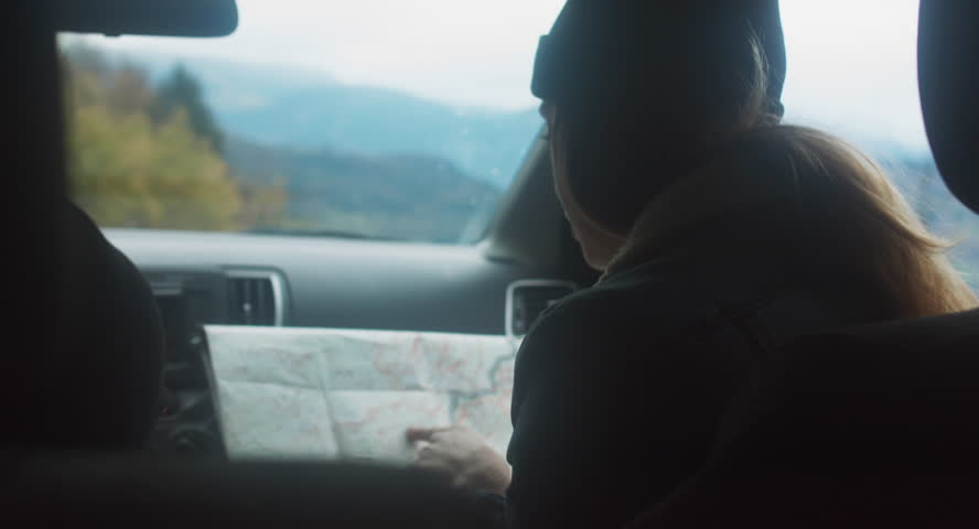 Rear view shot of couple traveling by car. Woman holding map, searching for the right way. Couple on a road trip. 4K UHD #33164071