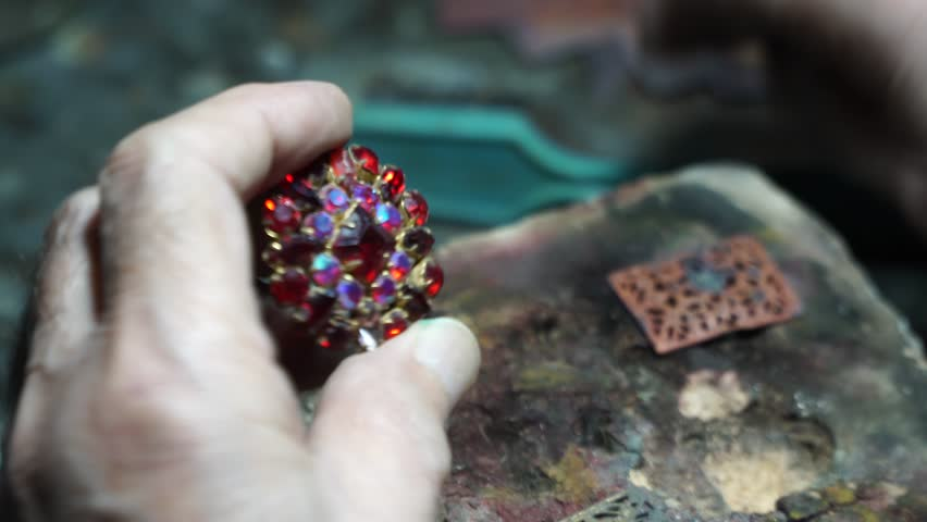 Video shooting of hands of the jeweler from a close distance. The old jeweler is working on the creation of jewelry