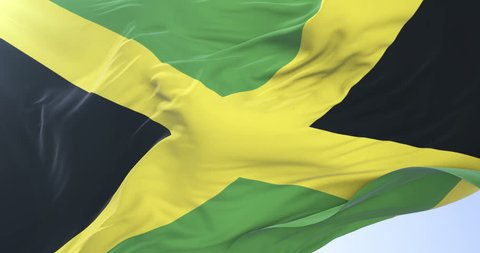 Flag of Jamaica waving at wind with blue sky in slow, loop