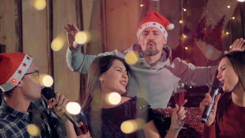 Group of joyfull friends singing karaoke having fun at Christmas party. 4K.
