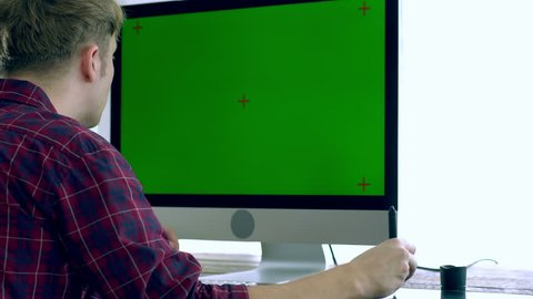 A caucasian male freelance designer, programer working at Home with all in one unit computer with green screen, laptop, a pen tablet and other electronics peripheral on the wooden table on a bright mo