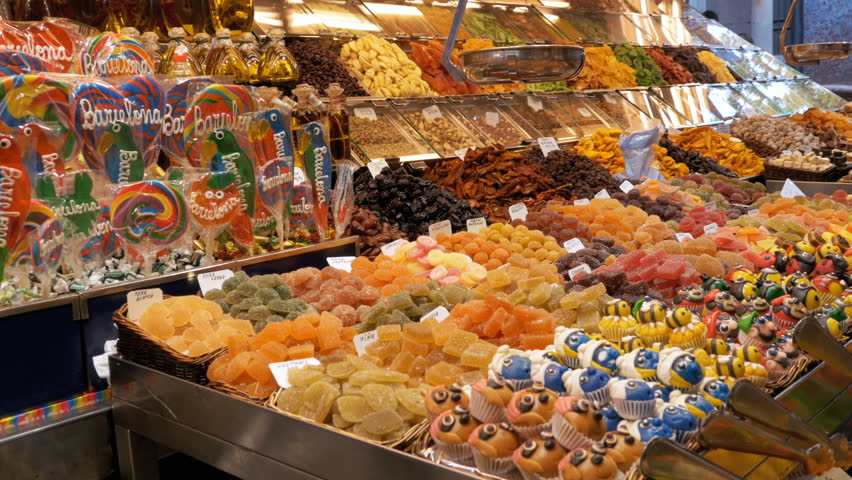 Large Counter with Colorful Sweets with Various Assorted Chocolate Candy in La Boqueria Market. Barcelona, Spain. Large counter with various Candy in glaze at Mercat de Sant Josep.