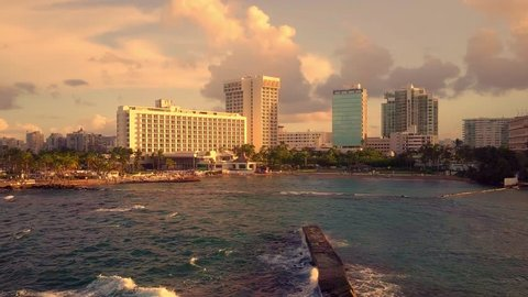 San Juan Puerto Rico at sunset. Unique view from the water as the waves crash against the rocks