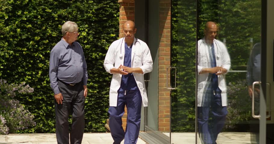 4K Overjoyed senior man getting good news from the doctor outside hospital building