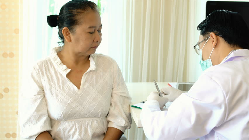Locked shot with asian middle-aged female patient with coughing and consulted the young doctor, used stethoscope listening on back to function of lungs in examination room | Shutterstock HD Video #33277201