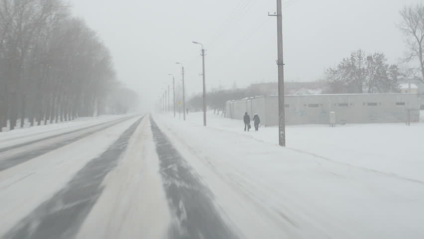 car go on road near small town and snowstorm snow falling. people walk. front car window view.