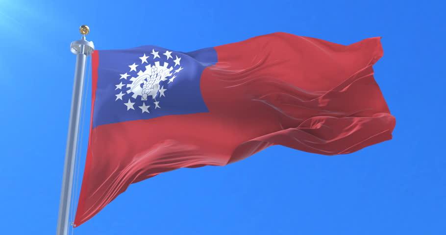 Flag of Myanmar or Union of Burma waving at wind in slow in blue sky, loop