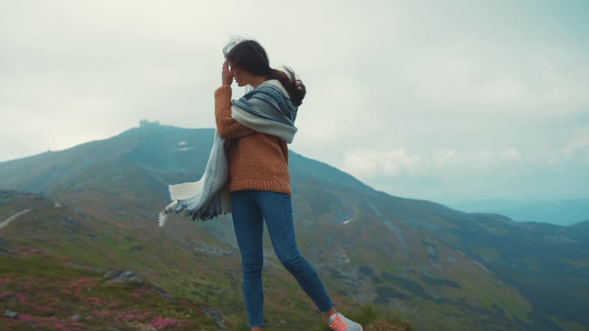 Attractive, young, fit woman in a sport outfit and stylish poncho standing on the rocky mountain top and admiring distant mountain hills in a strong wind. Pure nature, adventure time, relaxation. | Shutterstock HD Video #33295531