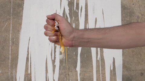 Hand crushing a raw egg against paint splashed wall