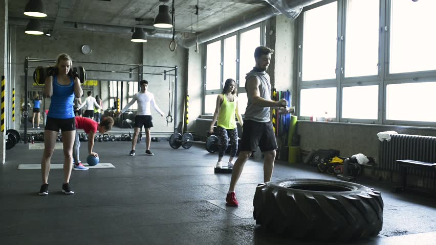 Young people in crossfit gym working out with various equipment.