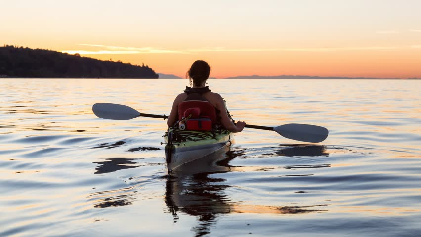 Cinemagraph of a woman enjoying the beautiful ocean scenery on a sea kayak during a vibrant sunset. Taken near Jericho Beach, Vancouver, British Columbia, Canada. Still image continuous loop animation