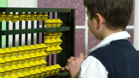 Pupil dressed up as teacher holding abacus in a classroom.