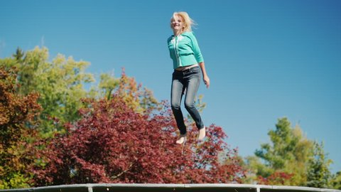 Active lifestyle. A middle-aged woman jumps high on a trampoline. Against the sky