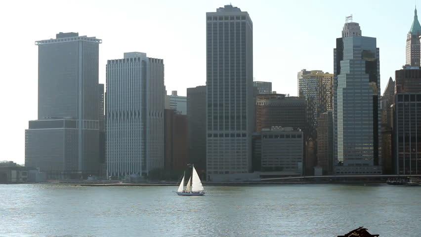 A sailboat cruises on the East River near downtown Manhattan | Shutterstock HD Video #3334811
