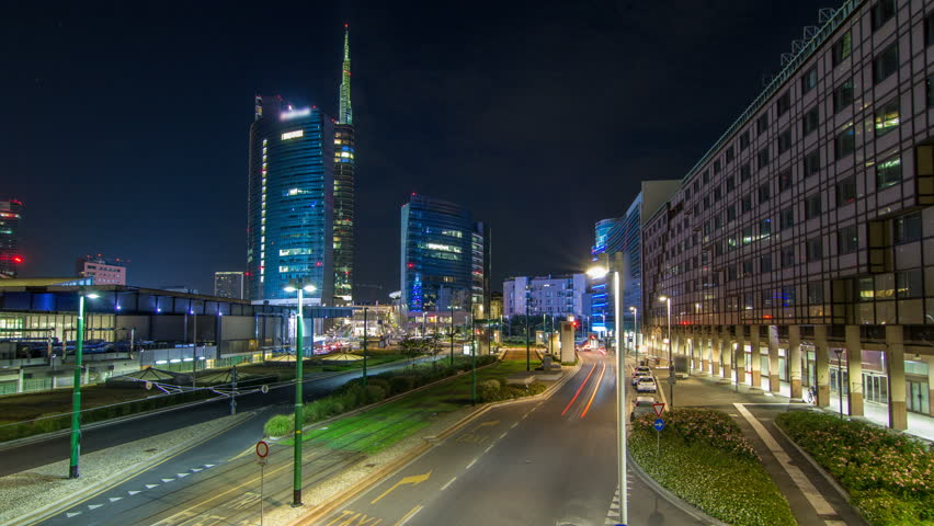 Milan skyline with modern skyscrapers in Porta Nuova business district night timelapse in Milan, Italy. Traffic on the road. Light in windows. Top view from bridge