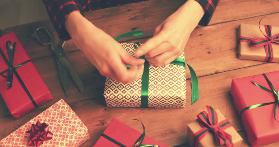 gift wrapping. woman tie a green ribbon bow