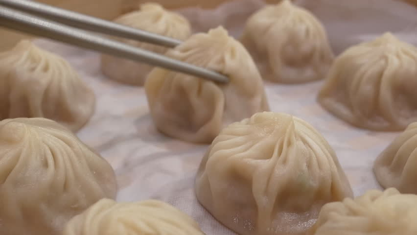 Motion of woman eating soup dumpling buns with chopsticks in restaurant in Taipei Taiwan with 4k resolution.