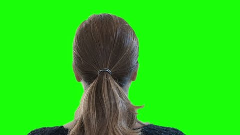 Ponytail Girl Head In Green Screen Background. Back head of a woman looking to green screen. Shot behind model shoulders.
