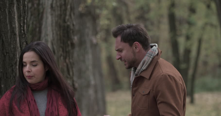 Couple quarreling in autumn forest park 4k video. Young angry overweight woman hits with flower in man face and goes away. Fail romance date. Love story concept