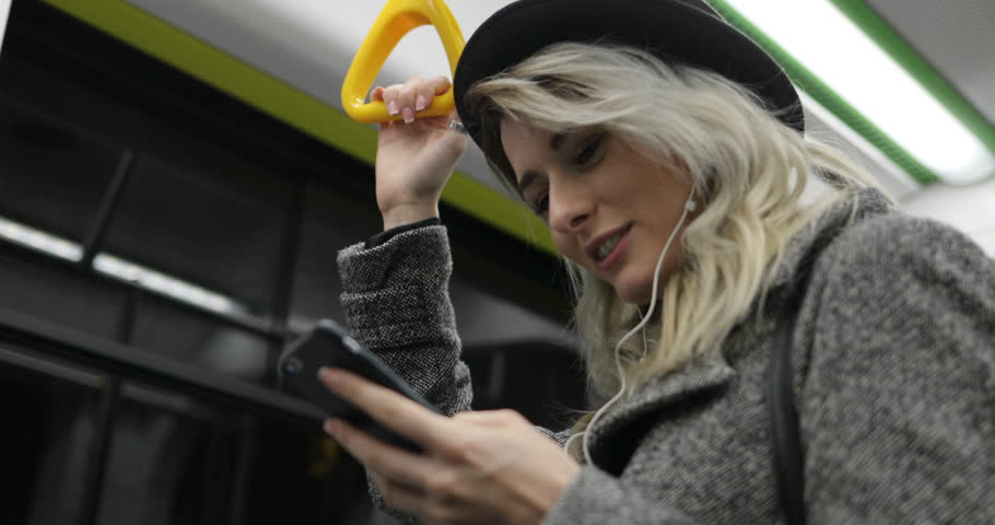 Portrait of cute girl in headphones holds the handrail, listening to music and browsing on mobile phone in public transport. City lights background #33427591