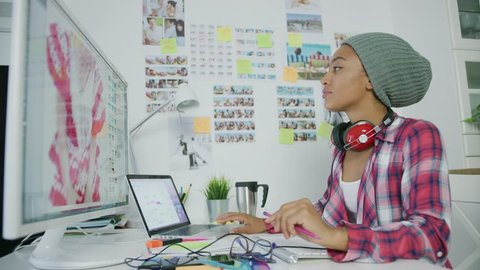 Young trendy model in hat wearing headphones and posing at working desktop with gadgets while working with computer in office.