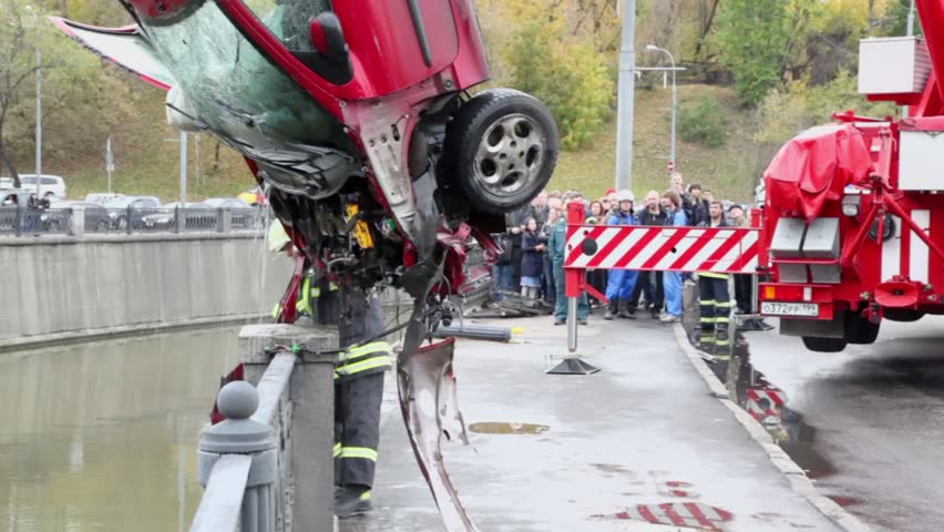 MOSCOW - OCT 9: EMERCOM serviceman takes part of crashed car which hangs on crane at quay of Yauza river, Oct 9, 2011, Moscow, Russia.