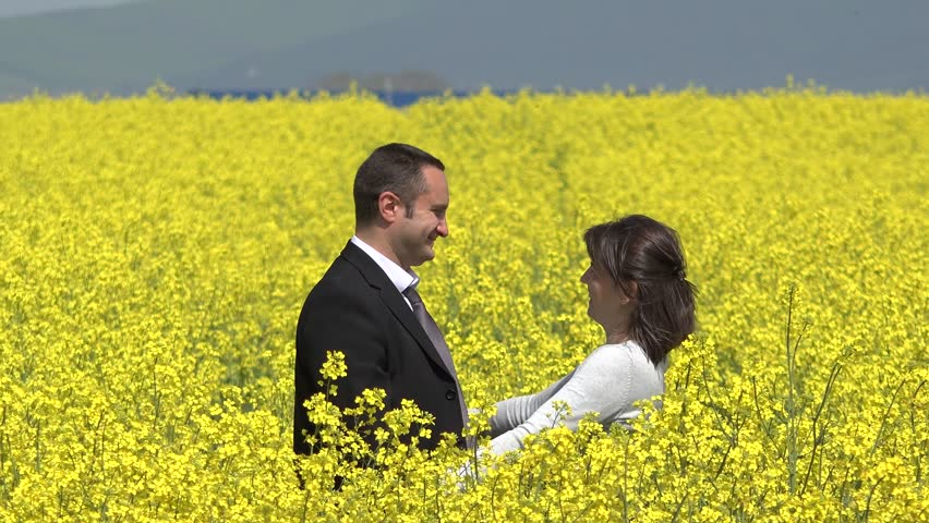 Couple of lovers embrace and he looked into each other's eyes in blossom rape field