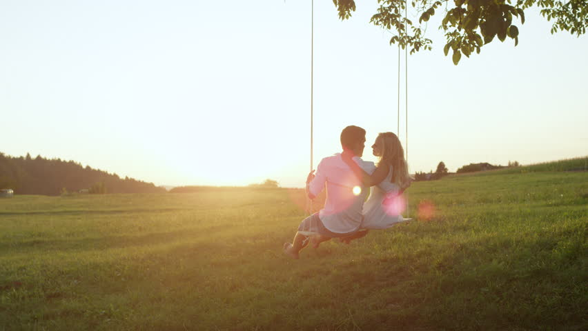 SLOW MOTION COPY SPACE: Embraced girlfriend and boyfriend on a tree swing kiss in sunset filled countryside. Couple bonds on a summer date in nature, hugging and sharing a kiss on a swaying rope swing | Shutterstock HD Video #33457411