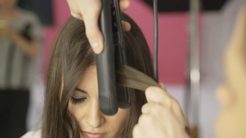 Beautiful woman with brown hair is having it treated with a curling iron by a hairdresser. Handheld real time establishing shot