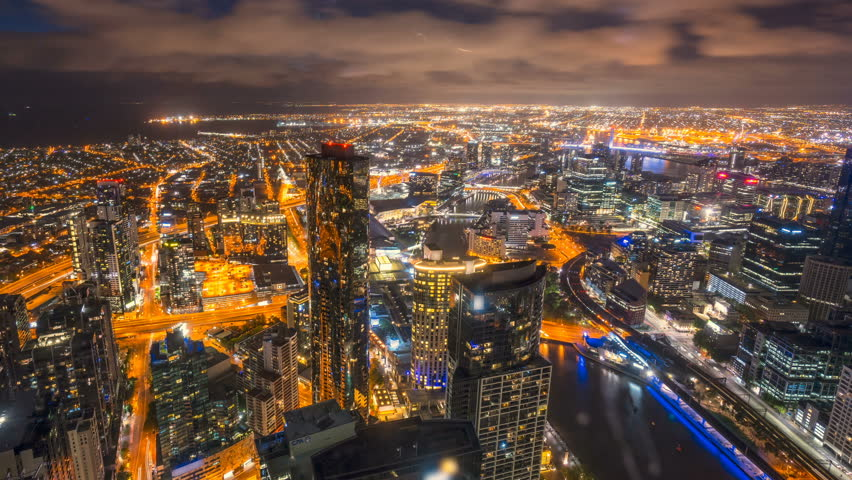 Rolling Clouds, sun rays burst through the clouds during sunrise. 4k time lapse of Melbourne city skyline, view from high level building. Pan right