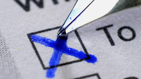 Cross in tick box, voting and elections. Extreme close up.