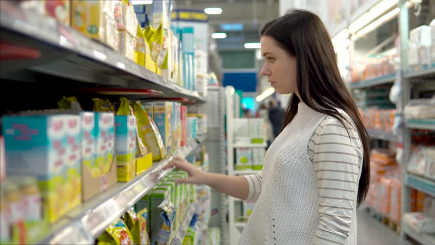 Young woman chooses baby food in the supermarket, Mother chooses food for their child in the market, girl stands near the supermarket shelf and selects the products | Shutterstock HD Video #33505540