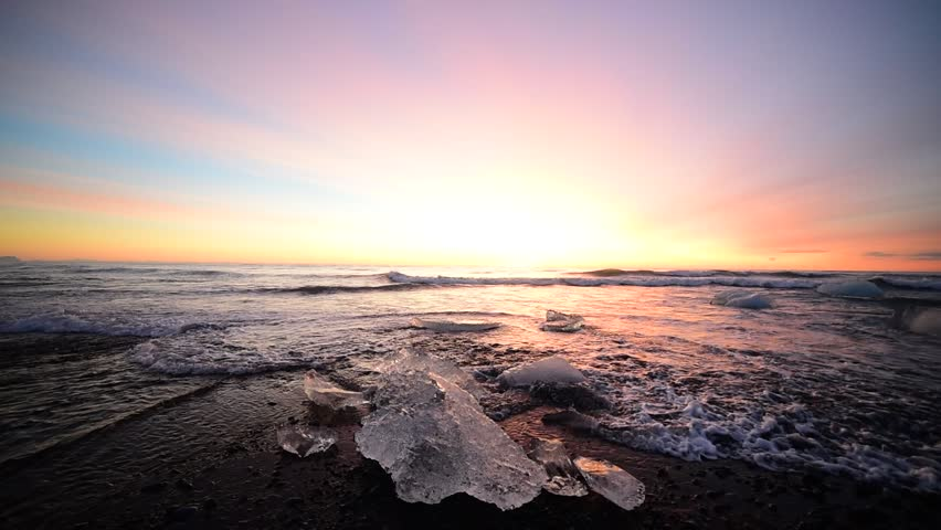 Iceland, Diamond black sand beach - winter calmness sunrise at the sea. Waves splashes on ice which shining at sun rays light on black sand coast