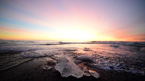 Iceland, Diamond black sand beach - winter calmness sunrise at the sea. Waves splashes on ice which shining at sun rays light on black sand coast