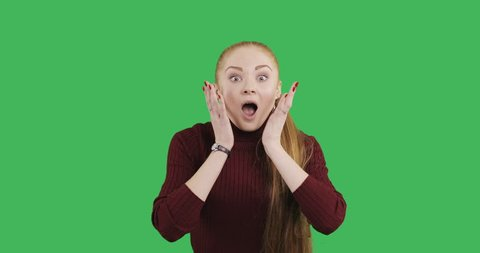 Female caucasian model with a long red hair is very surprised. Young woman with a great impression on green chroma key background.