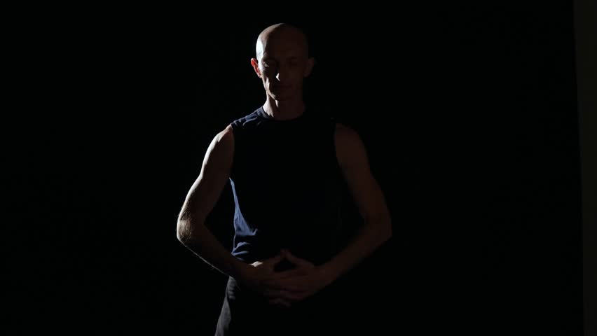 Half-lit silhouette of a man stretching in a darkened room with a single source of light. He is lifting his arms up over his head, stretching them to each side.