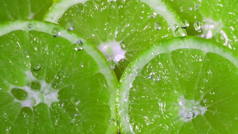 Green Limes Cut with Water Drops Super Slow Motion
