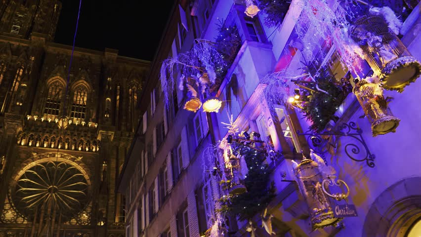 Christmas Market atmosphere in France Strasbourg with decorated buildings with lights and angels and Notre-Dame cathedral