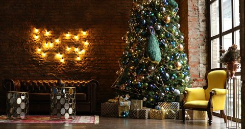 4K video footage of dark room with Christmas and New Year interior decoration. Green tree decorated with toys and flashing garland and yellow chair. Illuminated lamps on the grunge brick wall