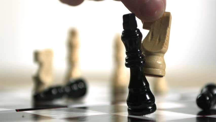 Hand using white knight to knock over king in chess in slow motion