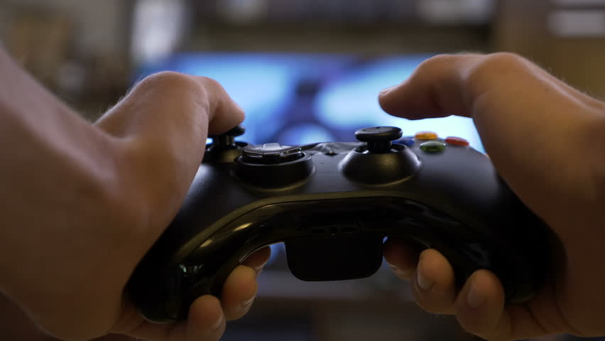 Closeup of young man hands playing video games on gaming console in front of TV widescreen
