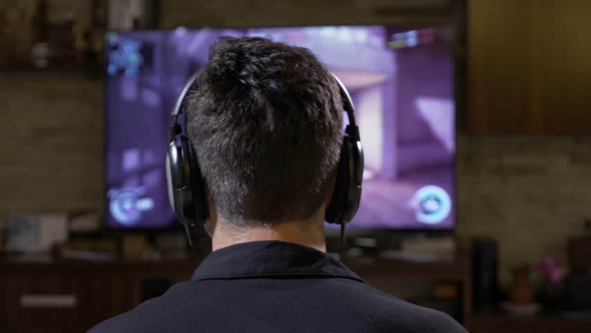 Back view of male gamer guy wearing headphones playing fps action shooter video game on TV console at home | Shutterstock HD Video #33552661