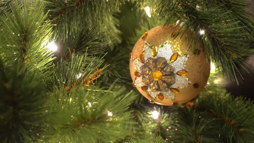 Greeting Season concept. Gimbal shot of ornaments on a Big Christmas tree with decorative light and falling snow in 4k (UHD)