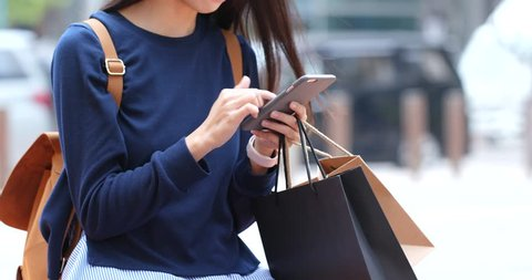 Shopping woman with paper bag and smart phone
