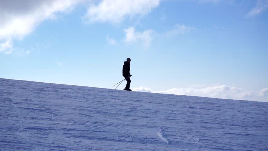A male skier silhouette in a ski suit and ski goggles slowly skiing downhill on a cloudy blue sky background. Ski resort in the snowy mountain woods on a bright winter day.