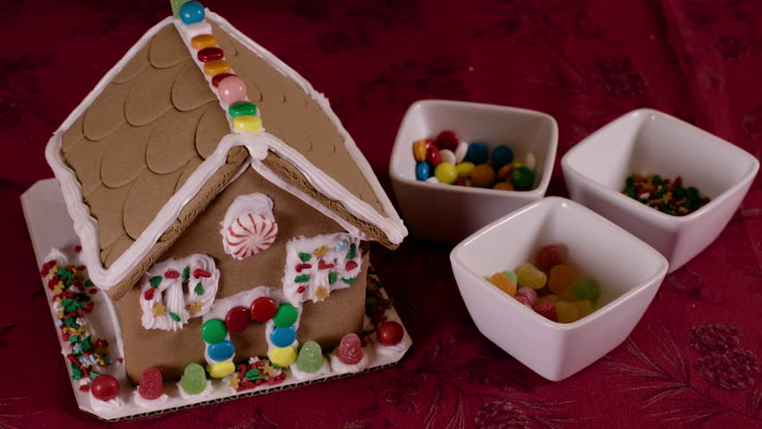 Placing candy on Christmas Gingerbread house