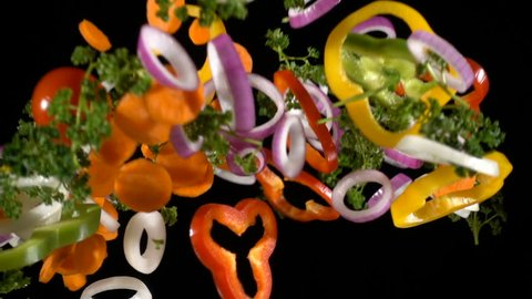 Falling cuts of plenty colorful vegetables isolated on black background, slow motion