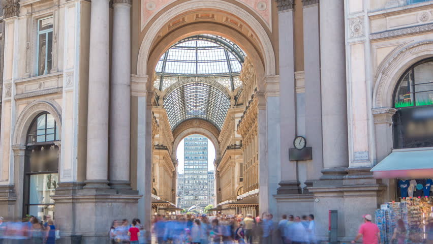 Entrance to the Galleria Vittorio Emanuele II from back side timelapse. This gallery is tourist attraction of Milan. Blue cloudy sky at summer day. People walking inside