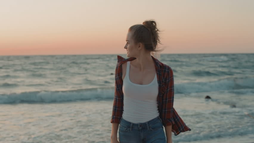 Young beauttiful female walking on beach during sunset or sunrise | Shutterstock HD Video #33613501