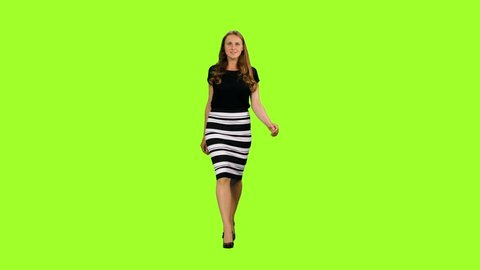 Beautiful woman in a black blouse and striped skirt walks on green screen background, Chroma key